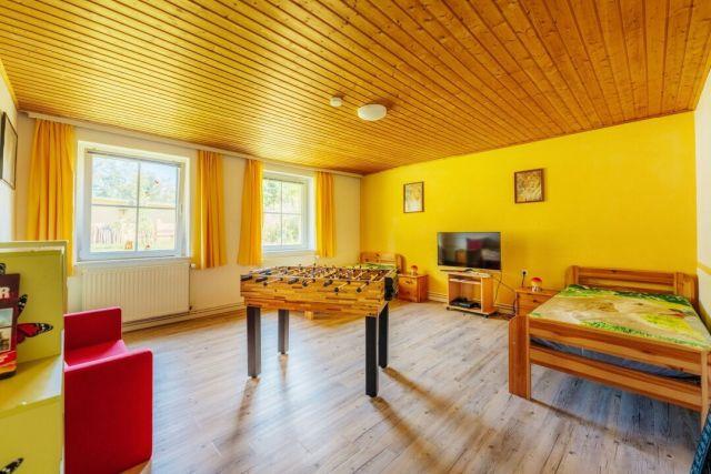 0586-09 Ferienhaus Zita Harz Spielzimmer mit Sitzcouch Betten und Spieltisch